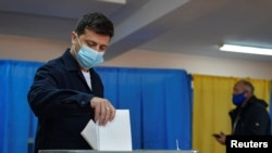 Presiden Ukraina Volodymyr Zelenskiy dengan mengenakan masker memasukkan surat suara untuk pemilu di tengah virus corona (Covid-19) di Kyiv, Ukraina, 25 Oktober 2020. (Foto: Reuters)