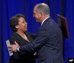Attorney General Loretta Lynch, left, and Louisiana Gov. John Bel Edwards hug after Edwards delivered remarks during a memorial service for three law enforcement officers. (Bill Feig/The Advocate via AP)