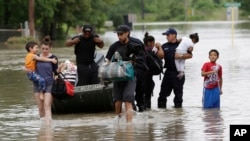 FILE - Residents walk through floodwaters after being evacuated from their flooded apartment complex, in Houston. Fort Hood, 320 kilometers northwest of Houston, has seen a dramatic increase in rainfall over the past few days.