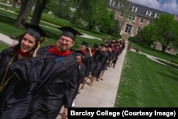 FILE: Barclay College graduates Taylor Mabry and Ryan Kucharek walk across campus to commencement ceremonies. Haviland, Kansas. May 2019