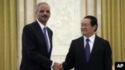 Le ministre américain de la justice Eric Holder et Zhou Yongkang, membre du comité permanent du Bureau politique du Comité central du Parti communiste chinois, à Pékin