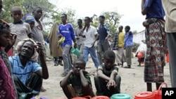 索马里儿童在境内一处安置营地等待领取救援食品。