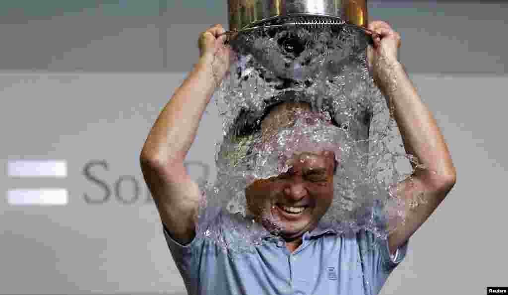 SoftBank Corp. Chief Executive Masayoshi Son dumps a bucket of ice water onto himself as he takes part in the ALS ice bucket challenge at the company headquarters in Tokyo, Japan.