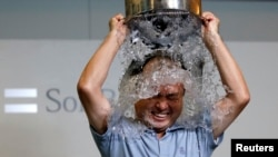 FILE - SoftBank Corp. Chief Executive Masayoshi Son dumps a bucket of ice water onto himself as he takes part in the ALS ice bucket challenge at the company headquarters in Tokyo August 20, 2014.