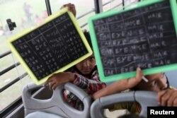 """Dua anak laki-laki menunjukkan papan tulis kecinya di dalam bus """"Harapan"""" yang dijadikan ruang kelas bergerak mereka, yang diparkir di daerah kumuh, dataran banjir sungai Yamuna, New Delhi, India 9 Agustus 2021. (REUTERS)"""