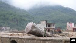 在同样遭受暴雨袭击的贵州省,一民警6月6日走过该省望谟县一座受灾桥梁
