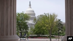 FILE - Capitol building is seen through the columns on the steps of the Supreme Court in Washington.