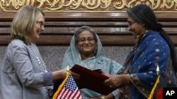 在孟加拉国总理哈西娜(中)微笑注视下,美国国务卿克林顿与孟加拉国外长迪普穆妮交换已签署的协议(5月5日)。