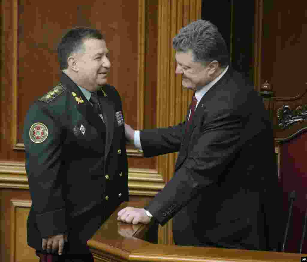 Ukraine's President Petro Poroshenko, right, speaks with new defense minister Stepan Poltorak in parliament in Kiev, Ukraine, Oct. 14, 2014.