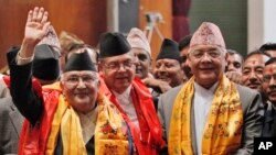 Nepal's newly-appointed prime minister Khadga Prasad Oli, left, waves to the media as he stands with other leaders of Communist Party of Nepal (Unified Marxist–Leninist), also known as CPN-UML, inside the Constituent Assembly in Kathmandu, Oct. 11, 2015.