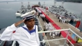 FILE- A Cambodian navy sailor salutes on a Chinese naval patrol boat during a handover ceremony at a Cambodian naval base at Ream in Sihanoukville province, southwest of Phnom Penh, on November 7, 2007.