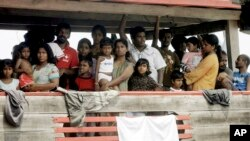 FILE - Sri Lankan migrants bound for Australia remain on board their boat docked at a port in Cilegon, Banten province, Indonesia, after they were intercepted by the Indonesian navy.