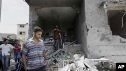 Warga Palestina mengamati rumah kepala polisi Gaza Tasyir al-Batsh yang hancur setelah terkena serangan rudal Israel hari Sabtu (12/7), menewaskan setidaknya 18 orang, di Gaza, 13 Juli 2014.