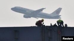 四川成都展览中心建筑工地上空飞过的中国国航飞机。(2020年2月26日)