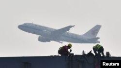 四川成都展覽中心建築工地上空飛過的中國國航飛機。 (2020年2月26日)