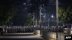 Riot police stand in formation on a road in a residential area in Yangon on February 25, 2021, as tensions rise following weeks of mass demonstrations against the military coup. (Photo by Ye Aung THU / AFP)
