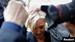 Des gardes du corps protègent la candidate à la présidentielle française Marine Le Pen, cible des œufs lancés par des manifestants lors de son arrivée à Dol-de-Bretagne, France, le 4 mai 2017.