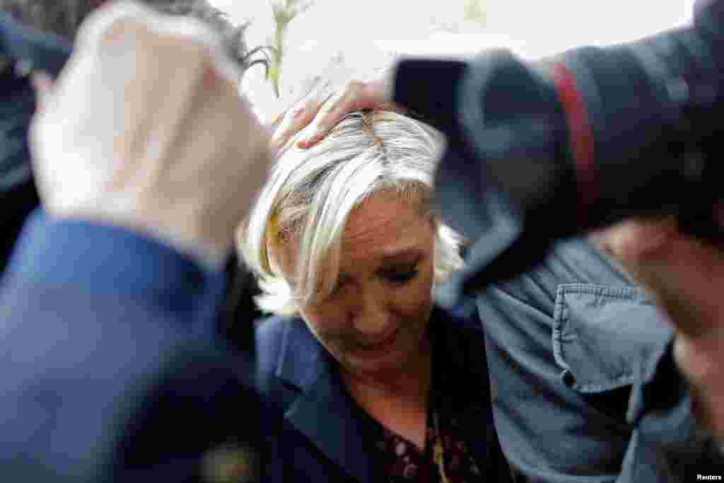 Marine Le Pen, French National Front (FN) party candidate for 2017 presidential election, is protected by bodyguards as demonstrators throw eggs during her arrival in Dol-de-Bretagne.