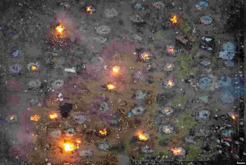 بھارت کے دارالحکومت دہلی میں کرونا وائرس سے ہلاک ہونے والوں کی اجتماعی آخری رسومات کی ادائیگی کے بعد شمشان گھاٹ میں چتائیں جل رہی ہیں۔