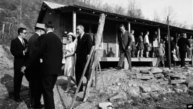 File - President Lyndon B. Johnson and his wife, Lady Bird, center left, leave home of Tom Fletcher, a father of eight who told Johnson he'd been out of work for nearly two years, Inez, Kentucky, April 24, 1964.