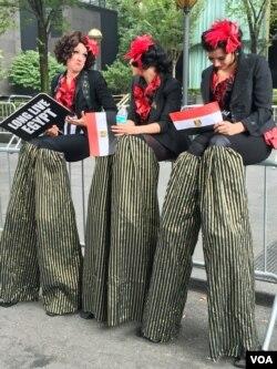 Women on stilts cheer for Egyptian President Abdel Fattah el-Sissi (VOA photo - C. Presutti).