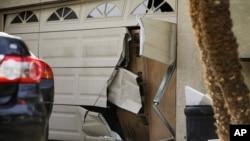 The battered garage door of Enrique Marquez is seen after a recent FBI raid, in Riverside, California, Dec. 9, 2015.