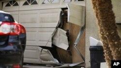 The garage door of Enrique Marquez's home is seen broken after a recent FBI raid, Dec. 9, 2015, in Riverside, California.