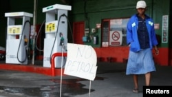 "A woman walks past a ""No Petrol"" sign at a fuel station in Harare, Zimbabwe, Oct. 9, 2018."