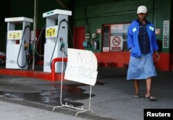 """A woman walks past a """"No Petrol"""" sign at a fuel station in Harare, Zimbabwe, Oct. 9, 2018."""