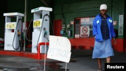 "FILE: A woman walks past a ""No Petrol"" sign at a fuel station in Harare, Zimbabwe, Oct. 9, 2018."