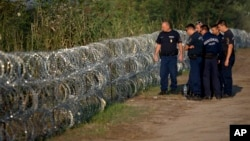 Hungarian police inspect a barbed wire fence on the border with Serbia, in Roszke, Hungary, Aug. 29, 2015.