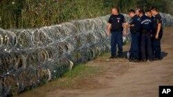 Macar polisi Sırbistan sınırına örülen dikenli telleri inceliyor
