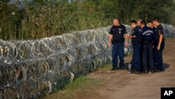 匈牙利的警察检查与塞尔维亚边界的铁丝网(2015年8月29日)