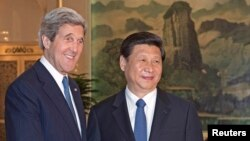 U.S. Secretary of State John Kerry (L) is greeted by Chinese President Xi Jinping shortly before their private meeting at the Great Hall of the People in Beijing April 13, 2013.