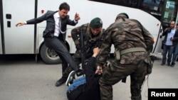 Seorang demonstran ditendang oleh Yusuf Yerkel (kiri), penasihat Perdana Menteri Recep Tayyip Erdogan, saat polisi menahan demonstran itu dalam protes melawan kunjungan Erdogan di Soma (14/5).