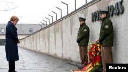 FILE - German Chancellor Angela Merkel observes a moment of silence as she lays a wreath during a ceremony at the memorial in the former Nazi concentration camp in Dachau, near Munich, May 3, 2015, to mark the 70th anniversary of the liberation of the camp.