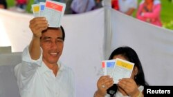 Jakarta governor and presidential candidate from the Indonesian Democratic Party-Struggle (PDI-P) party, Joko Widodo, and his wife Iriana show their ballot papers during voting in the parliamentary elections in Jakarta, April 9, 2014.