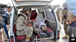A Pakistani paramilitary soldier sits in the back of a vehicle next to the lifeless body of his colleague who was killed by gunmen during a gun battle at a hospital, in Quetta, Pakistan, June 15, 2013.