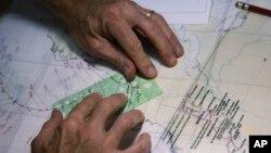 Специалист ВМС США Дэйв Робертс наносит на карту предполагаемый маршрут урагана «Сэнди». Национальный центр изучения ураганов (NHC), Майами, Флорида. 29 октября 2012 года