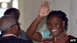 អតីតជំទាវទីមួយនៅកូតឌីវ័រលោកស្រី Simone Gbagbo គ្រវីដៃ នៅពេលដែលលោកស្រីមកដល់តុលាការយុត្តិធម៌ក្រុង Abdijan នាថ្ងៃទី២៣ ខែកុម្ភៈ ឆ្នាំ២០១៥។