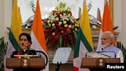 Myanmar's State Counsellor Aung San Suu Kyi (L) reads a joint statement as Indian Prime Minister Narendra Modi