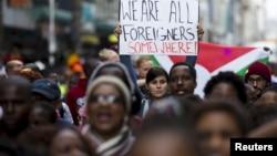 """在南非的德班发生排外暴力事件后,人们游行示威,有人举着的标语牌上写着""""我们在某个地方都是外国人"""""""