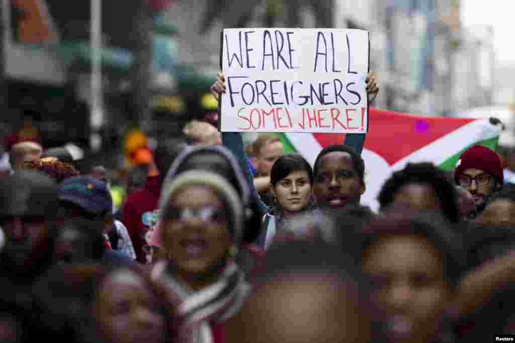 "A woman holds up a sign reading ""We are all foreigners somewhere!"" during a peace march after anti-immigrant violence flared in Durban, April 16, 2015."