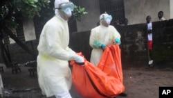 身穿防护服的利比里亚卫生人员抬着疑似死于埃博拉者的尸体