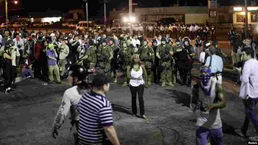 Demonstrators protesting against the shooting of Michael Brown are surrounded by police in riot gear in Ferguson, Missouri, Aug. 19, 2014.
