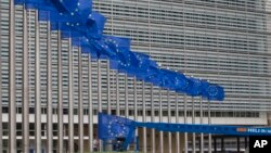 Workers adjust the EU flags in front of EU headquarters in Brussels, Belgium, June 22, 2016. Voters in the United Kingdom are taking part in a referendum that will decide whether Britain remains part of the European Union or leaves the 28-nation bloc.