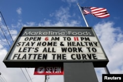 "A neighborhood market marquee reads ""stay home and healthy, lets all work to flatten the curve"" in Seattle, Washington, U.S. April 2, 2020. (REUTERS/Jason Redmond)"