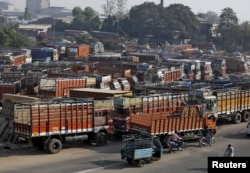 FILE - Trucks are seen parked in an open lot near a national highway on the outskirts of Ahmedabad, India, Dec. 2, 2015.