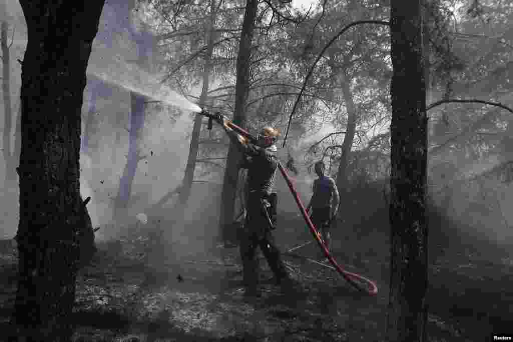 Volunteer firefighters extinguish a forest fire in Kareas suburb, east of Athens, Greece.