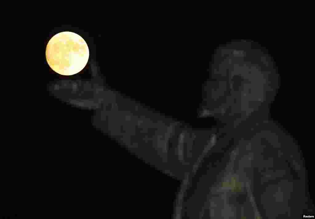 "Bulan purnama ""supermoon"" terlihat di belakang patung pendiri Uni Soviet, Vladimir Lenin, di Baikonur, Kazakhstan."